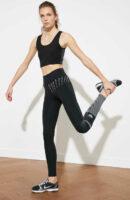 Sportovní dámské černé legíny oživené vzorem na nohavici